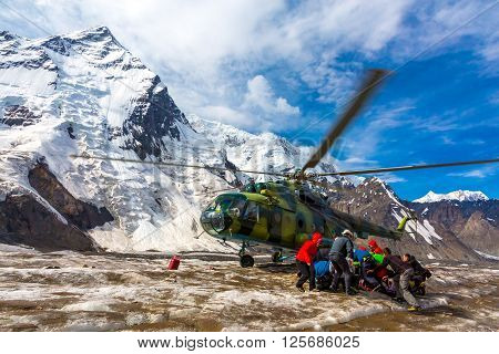 Transport Helicopter Taking Off from Ice Field of Massive Mountain Glacier People Holding Luggage to Protect from Wind Blowing of Rotor