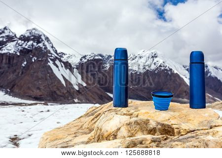Two Blue travel thermoses Thermo Bottles and Cup on Bright Textured Marble stone Mountain Range and overcast sky on Background