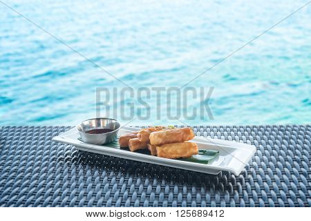 Vegetable fried spring rolls served with bittersweet sauce on wicker table and water background