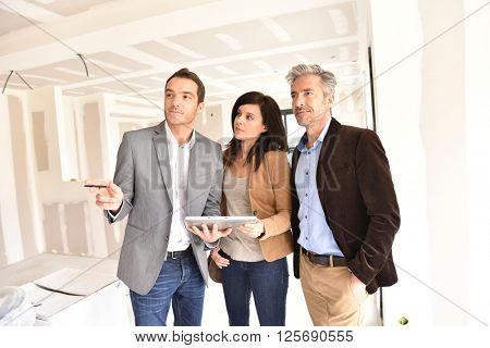Couple with realtor visiting house under construction
