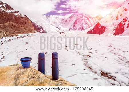 Two Blue travel thermoses and Cup on Bright Textured Marble stone Many Orange Camping Tents of Mountaineering Expedition Base Camp and High Peaks on Background