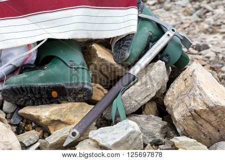Composition of Mountain Climbing Footwear and Gear in Stones Green Plastic High Altitude Old Boots and Vintage Style Ice Axe
