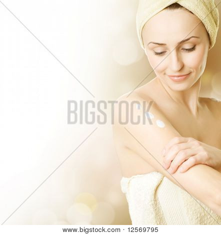 Beautiful Young Woman applying moisturizer.Skincare concept