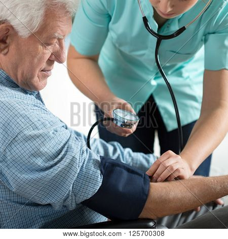 Young attractive nurse checking the elderly man's hypertension