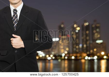 One business man wear black suit stand on blur modern building background