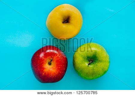 Top view of Red green and yellow apple different in colors on a blue background Diversity Concept