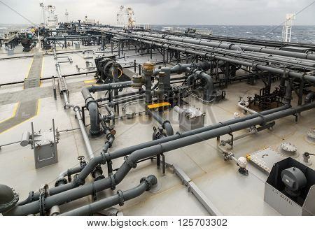 Cargo deck of oil product carrier in the sea during rain.