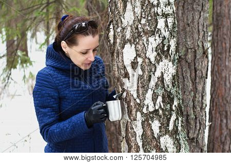 Beautiful woman in a spring forest birch SAP collects in a Cup