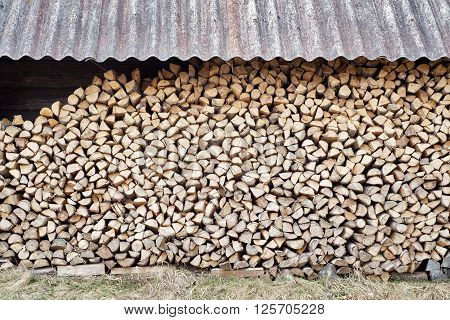 stack of chopped firewood in the woodshed