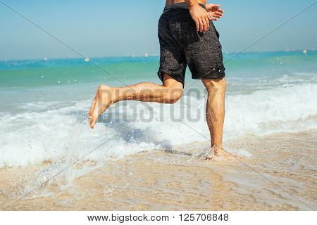 Low section of a man running into sea.