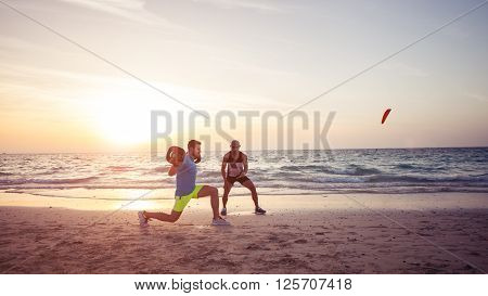 Man doing fitness on the beach with the help of personal trainer. Warm tone lens flare.