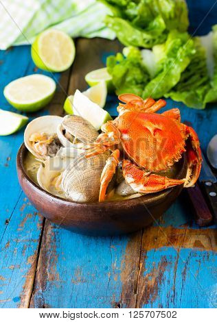 Seafood soup of clams and crab in clay bowl on wooden blue background.  Mariscal or paila marina