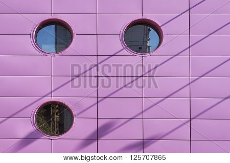 Pink modern wall with round windows close up