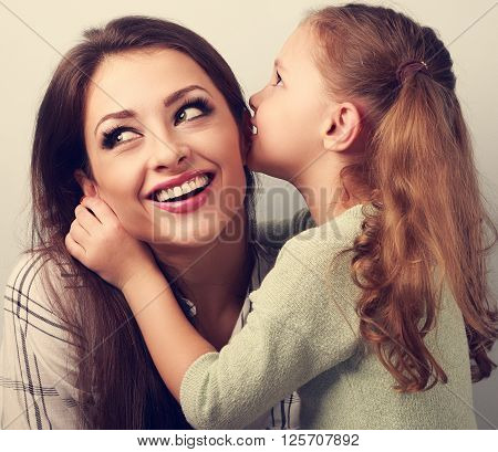 Happy Cute Kid Girl Whispering The Secret To Her Smiling Mother In Ear With Fun Face. Toned Closeup