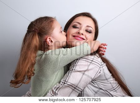 Cute Kid Girl Kissing And Cuddling Her Enjoying Beautiful Mother In Studio On Blue Background