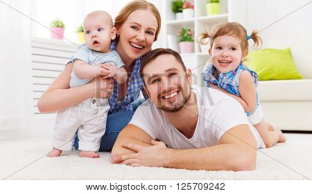 happy family mother father and two children playing and cuddling at home on floor