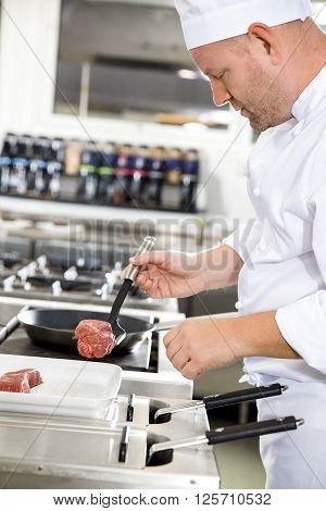 Close-up of a chef prepares beef steak dish in a pan at a professional kitchen. Gourmet restaurant or hotel.