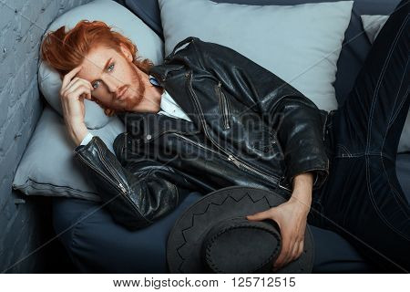 Redhead metrosexual man in casual style lies on the couch.