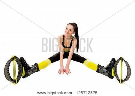 smiling young woman brunette with long hair in a kangoo jumps shoes sitting legs apart. Isolated on white background in studio. Shot at wide angle