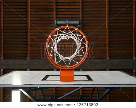 Photo of an indoor basketball hoop from below.