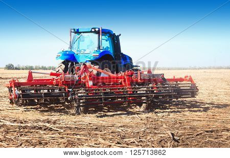 Blue tractor in an open field on a sunny day