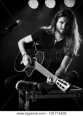 Photo of a young man with long hair and a beard playing an acoustic guitar on stage with lights and concert atmosphere.
