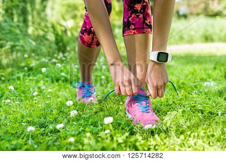 Healthy summer lifestyle - Girl runner getting ready for weight loss exercise tying running shoes laces wearing smartwatch activity tracker for an active living. Cute pink floral tights and outfit.