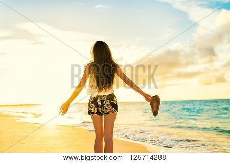 Freedom woman carefree dancing relaxing on beach in sunset. Young people summer lifestyle vacation travel. Vitality healthy living concept.