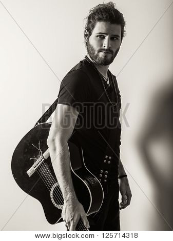 Photo of a young attractive man with long hair and beard standing and holding an acoustic guitar. Filtered to look vintage.