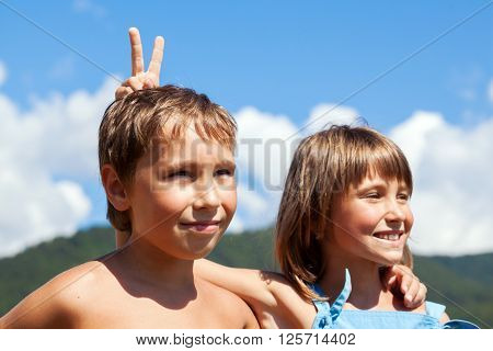 Portrait of smiling young boy and girl in friendly embrace each other's shoulders