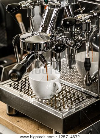 Photo of an espresso being made with a professional coffee machine.