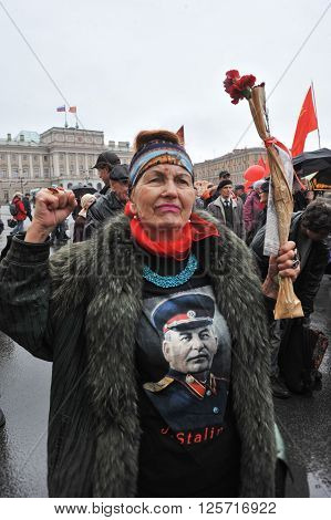 ST. PETERSBURG RUSSIA - MAY 1: Woman with a portrait of the Russian dictator Stalin T-shirt during a May Day demonstration on St. Isaac's square opposite the Mariinsky Palace in May 1 2010