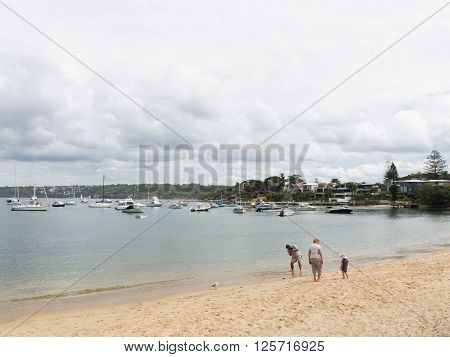 Sydney - March 1 2016: Sydney beach and people walk with the child and taking pictures from sea water Sydney Harbour March 1 2016 Sydney Australia
