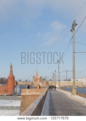 Moscow - January 7 2016: People walk by and large Moscow River bridge across the Moscow River and see the Kremlin and St. Basil's Cathedral winter day January 7 2016 Moscow Russia