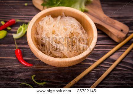 Ingredients of Asian cuisine - rice noodles leek lettuce red hot pepper on a dark wooden background