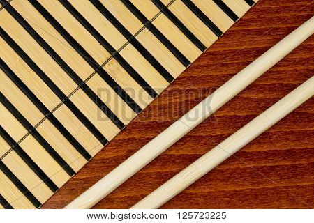 Chopsticks and bamboo mat over wooden background