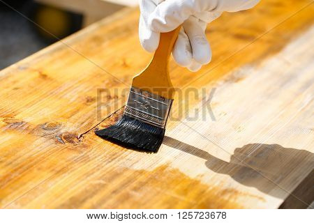 Carpenter holding a paintbrush over wooden surface protecting wood for exterior influences and weathering. Carpentry wood treatment hard at work home improvement do-it-yourself concept.