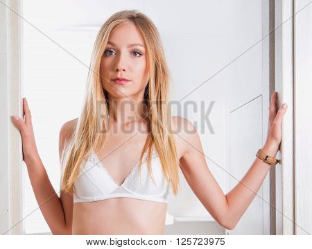 Young sexy blonde girl in white lace underwear standing on bathroom door