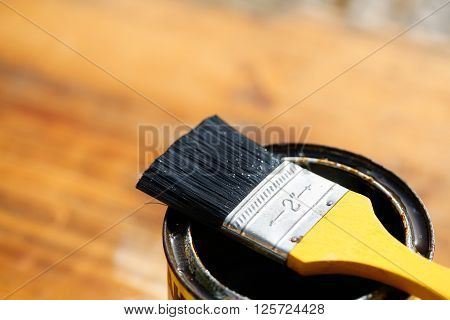 Brush resting on a tin can of protective paint for wood treatment against weathering insects and fungus. Outdoor protection carpentry hard at work home improvement do-it-yourself concept.