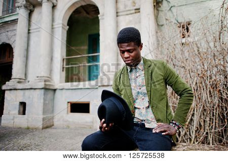 Fashion Portrait Of Black African American Man On Green Velvet Jacket And Black Hat, Sitting At Fell
