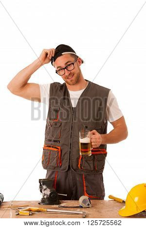 Handyman in work clothing having a break drinkng beer isolated over white.