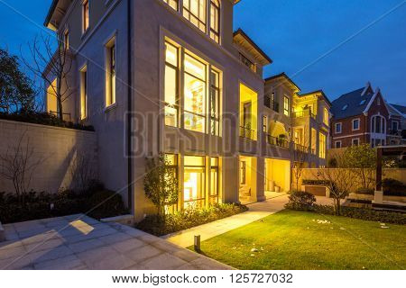 luxury houses with yellow light in modern villa at night