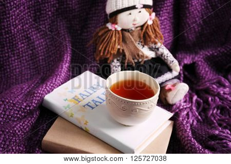 Rag doll with fairy tales books and cup of tea on bedspread. Childhood concept