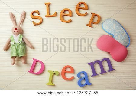 Text Sleep Dream, masks and rabbit toy on light wooden table, top view