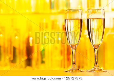 Two flute glasses standing on bar counter topped up with champagne