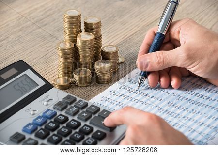 Close-up Of A Businessman Calculating Financial Report