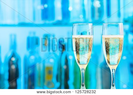 Two flutes with champagne standing at the bar counter in the blue lighting