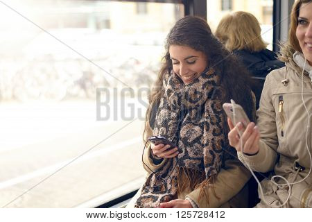 Happy brunette woman reading a message on her mobile phone while sitting in a bus public transport and technology concept