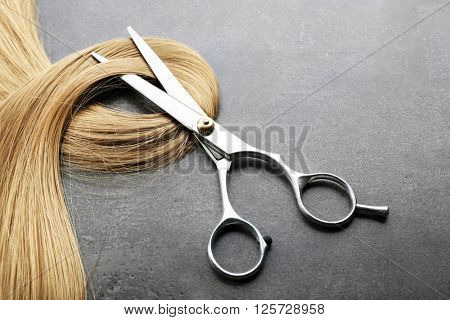 Hairdresser's scissors with strand of blonde hair on grey background