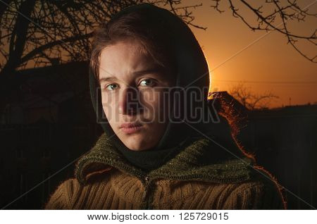 Russian cute girl peasant woman in a warm shawl at sunset
